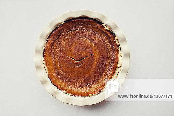 Draufsicht auf die in Teller servierte Torte auf weißem Tisch