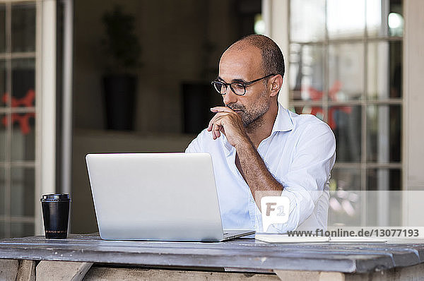 Businessman using laptop computer while sitting at table in office