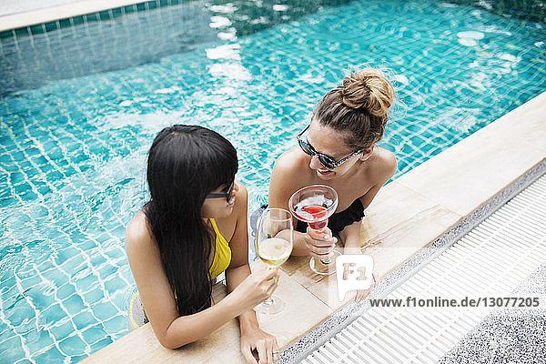 Hochwinkelaufnahme von Frauen  die im Schwimmbad auf Getränke anstoßen