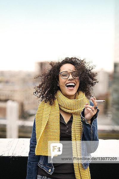 Fröhliche Frau hält Zigarette in der Hand  während sie auf der Gebäudeterrasse steht