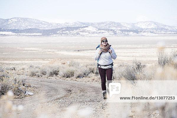 Wanderin in voller Länge im Winter in der Wüste unterwegs