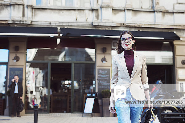 Woman with shopping bags walking on city street