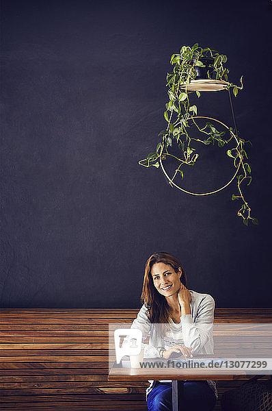Porträt einer glücklichen Frau  die an einem Café-Tisch sitzt