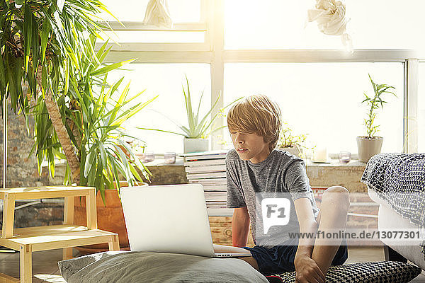 Boy looking at laptop computer while sitting on floor against window