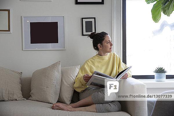 Frau hält Zeitschrift in der Hand und schaut weg  während sie zu Hause auf dem Sofa sitzt