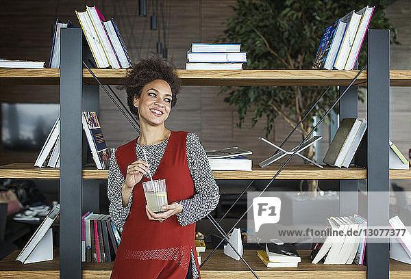 Nachdenkliche glückliche Frau hält Limonade in der Hand  während sie gegen ein Bücherregal steht
