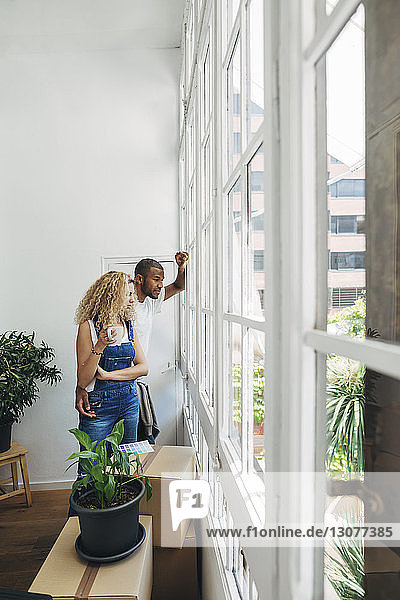 Couple looking through window while standing in new house