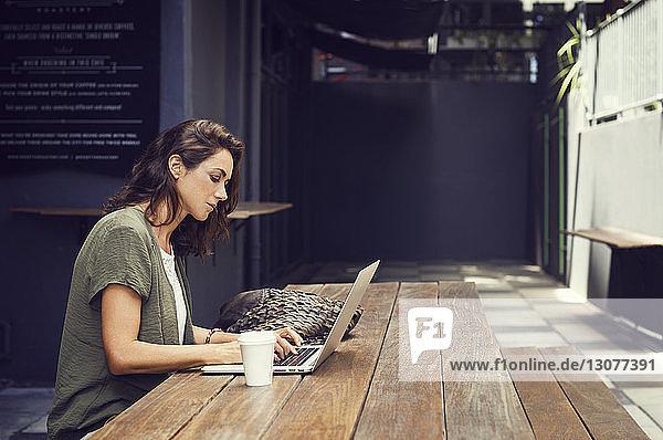 Seitenansicht einer Frau mit Laptop im Straßencafé