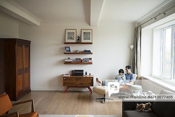 Father and son using tablet while sitting in living room at home