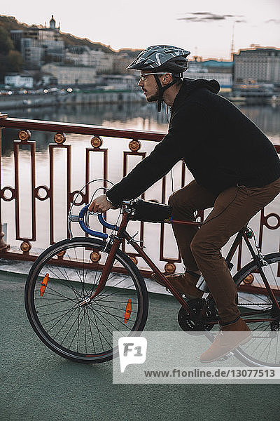 Side view of male cyclist riding bicycle on bridge over river in city during sunset