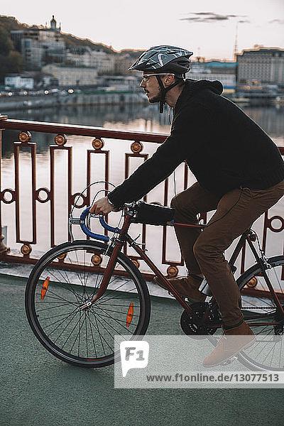 Seitenansicht eines männlichen Radfahrers  der bei Sonnenuntergang auf einer Brücke über einen Fluss in der Stadt Fahrrad fährt