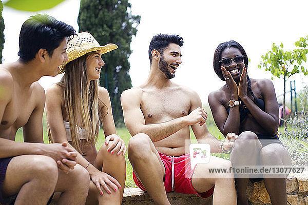 Cheerful multi-ethnic friends in swimwear sitting on retaining wall at yard