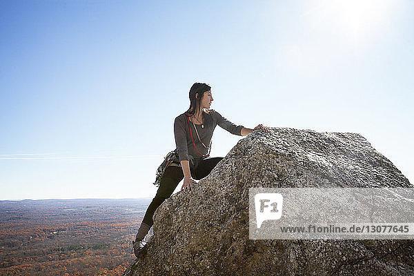 Frau schaut weg  während Felsen gegen den Himmel klettern