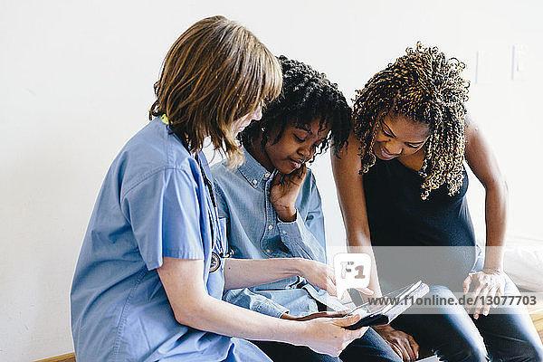 Arzt zeigt Tochter und Mutter Ultraschall am Tablet-Computer  während er im Krankenhaus sitzt