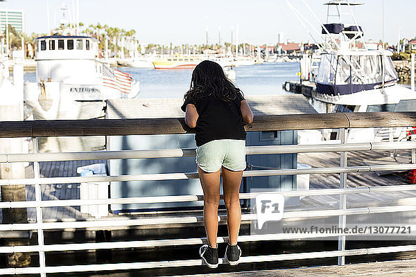 Rückansicht eines Mädchens  das auf einem Geländer am Hafen steht