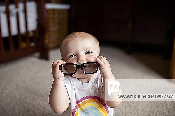 Hochwinkelporträt eines Mädchens mit Brille  das zu Hause sitzt