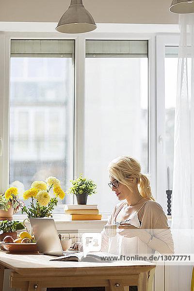 Frau mit Getränk mit Laptop-Computer  während sie zu Hause am Fenster sitzt