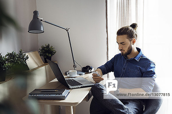 Man using mobile phone while sitting on chair by window at home