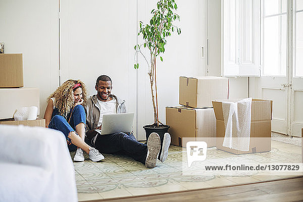 Smiling couple using laptop computer while sitting on floor at new house