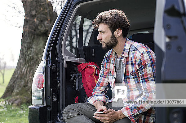 Thoughtful man sitting in car trunk at campsite