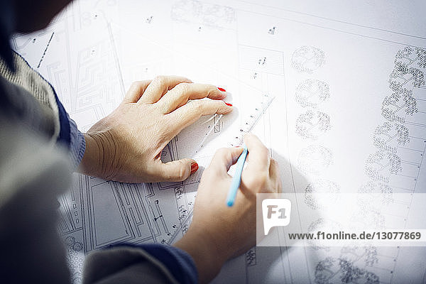 Female architect drawing design on paper in office