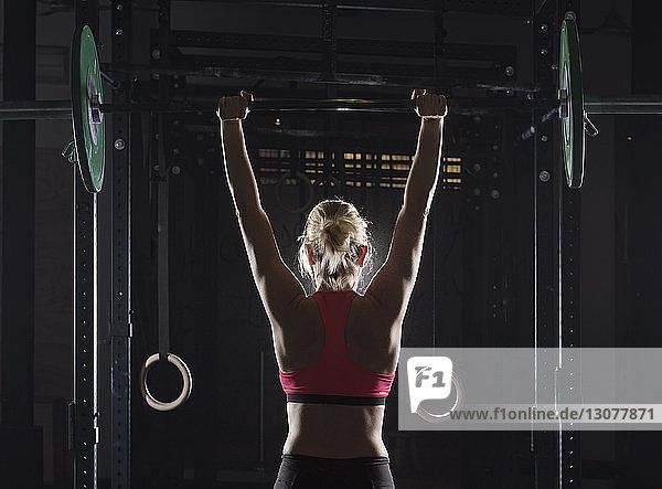 Rear view of female athlete picking barbell at gym