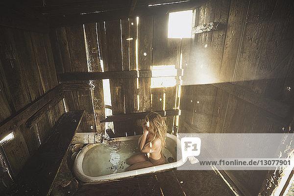 Hochwinkelansicht einer nackten Frau  die in der Badewanne eines alten Badezimmers kniet