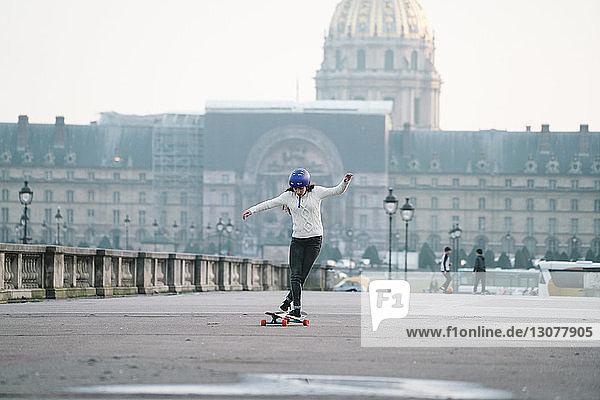 Skateboard fahrende Frau in voller Länge gegen Musee de larmee