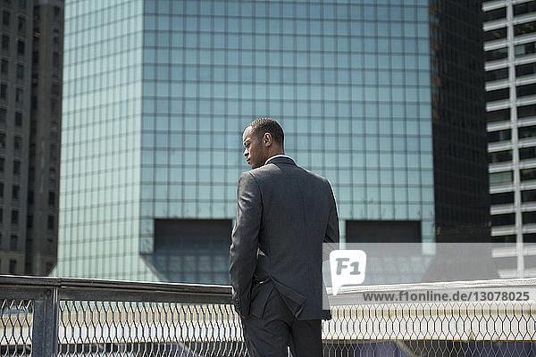 Rückansicht eines Geschäftsmannes  der sich gegen Bürogebäude stellt