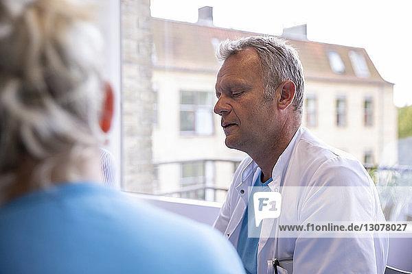 Männlicher Arzt bespricht sich mit einem Kollegen  während er in einer medizinischen Klinik sitzt