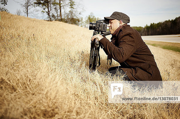 Side view of photographer with tripod crouching on grassy field