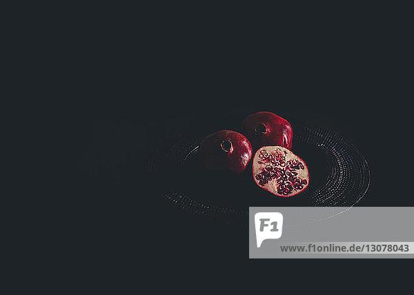 Hochwinkelansicht von Granatäpfeln auf Platzdeckchen vor schwarzem Hintergrund