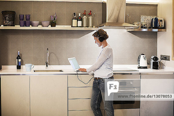 Side view of mature woman using laptop at kitchen counter