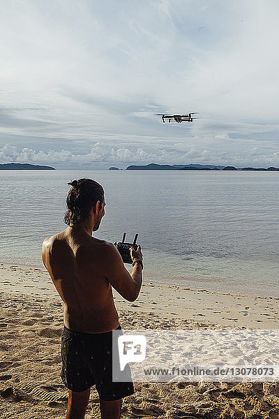Shirtless man flying drone while standing at beach