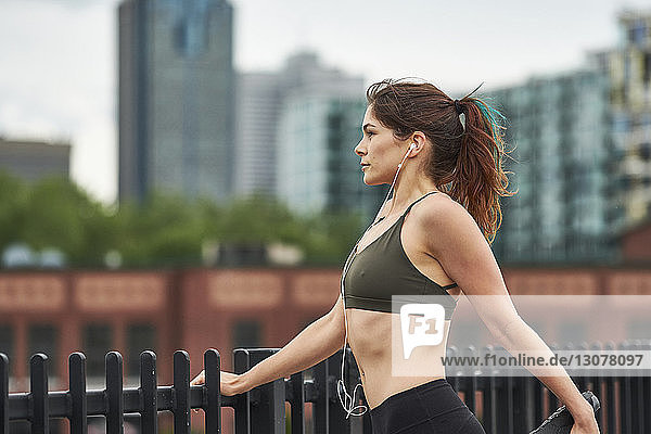 Confident woman exercising while listening music by railing in city