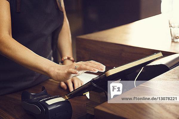 Mittelteil des Eigentümers benutzt digitales Tablett an der Kasse im Café