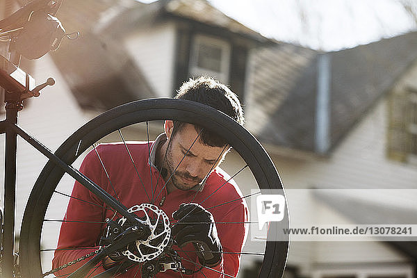 Athlete examining bicycle during sunny day