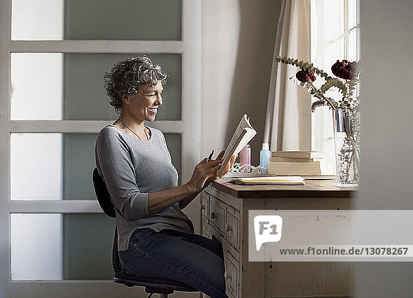Mature woman reading book on table at home
