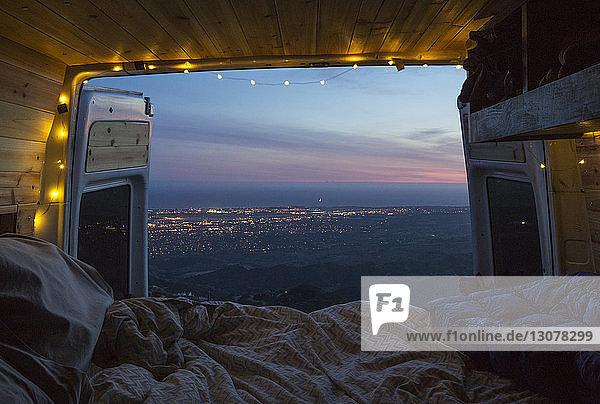 Szenische Ansicht der Landschaft gegen den Himmel vom beleuchteten Wohnmobil aus gesehen bei Sonnenuntergang
