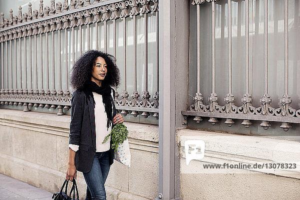 Frau geht in der Stadt auf einem Fußweg mit dem Geländer