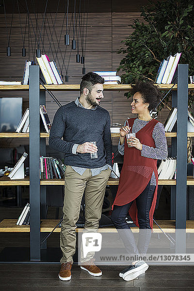 Happy business couple holding drinks while standing against book shelf in restaurant