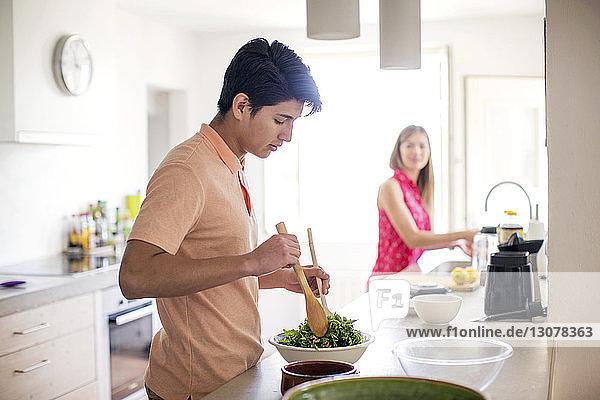 Seitenansicht eines Mannes bei der Salatzubereitung mit einer im Hintergrund stehenden Frau in der Küche