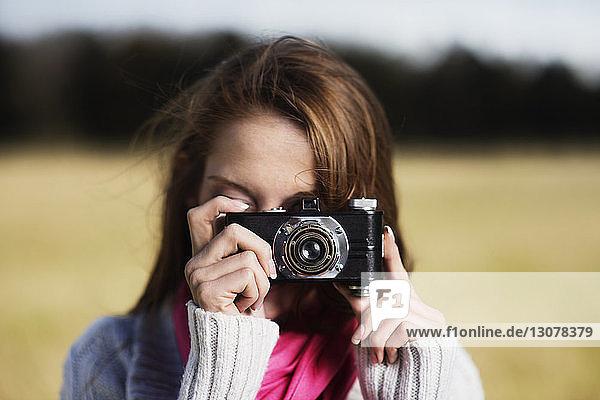 Nahaufnahme einer Frau im Pullover  die vor Ort durch eine Kamera fotografiert