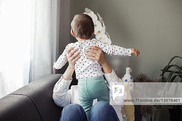 Woman holding baby girl while sitting on sofa at home