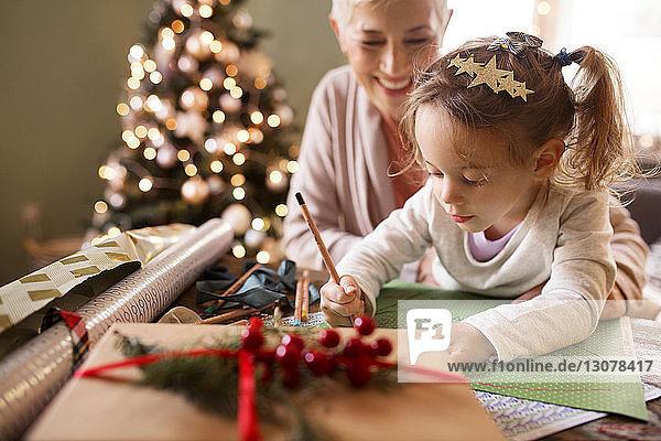 Großmutter betrachtet Enkelin an Weihnachten beim Zeichnen auf Papier