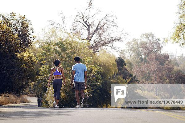 Rückansicht eines auf der Straße gehenden Paares