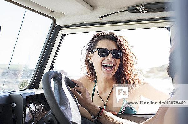 Fröhliche Frau mit Sonnenbrille im Gespräch mit einem Freund  der im Geländewagen sitzt