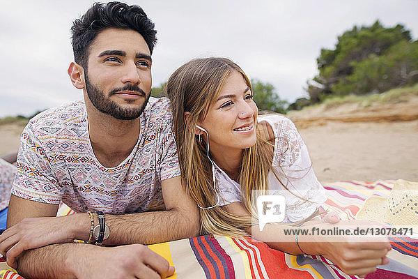 Nachdenkliches Paar schaut weg  während es auf einer Decke am Strand liegt