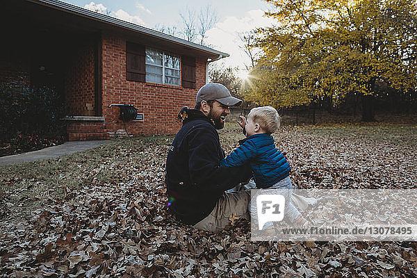 Glücklicher Vater spielt mit seinem Sohn  während er auf Herbstlaub im Hof sitzt
