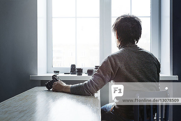 Rear view of male photographer holding camera and sitting on chair against window